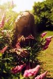 Frau im rosa Kleid mit rosa Blumen Lizenzfreie Stockfotografie