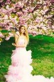 Frau im rosa Kleid nahe Blüte lizenzfreie stockbilder