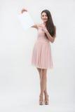 Frau im rosa Kleid zeigend auf Platzkopie Stockfotos