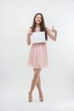 Frau im rosa Kleid zeigend auf Platzkopie Lizenzfreie Stockfotografie