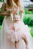 Frau im rosa Kleid zieht oben ihre kleine Tochter in der gleichen Kleidung im Park auf Lizenzfreie Stockfotos