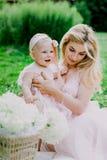 Frau im rosa Kleid zieht oben ihre kleine Tochter in der gleichen Kleidung im Park auf Stockfotografie