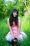 Frau im rosafarbenen Kleid, das auf den alten suitcas sitzt Stockfotografie