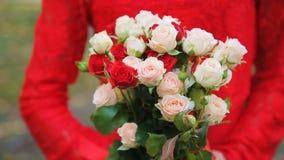 Frau im Rot, das einen Blumenstrauß von Blumen hält stock footage