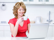Frau im Rot mit trinkendem Kaffee des Laptops Stockfotos