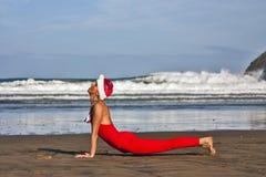 Frau im Rot und Weihnachtshut machen gymnastisch auf dem Strand Stockbild
