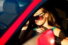 Frau im roten Auto Stockbild
