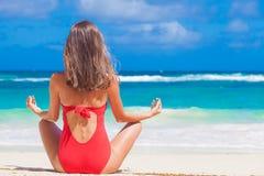 Frau im roten Badeanzug, der am Strand sich entspannt Mahe Insel, Seychellen Stockbilder