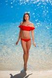Frau im roten Bikini auf Hintergrund des blauen Wassers lizenzfreie stockfotografie