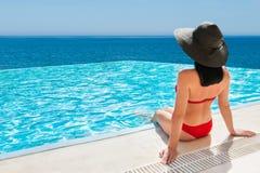 Frau im roten Bikini, der im UnendlichkeitsSwimmingpool übersieht das Meer sich entspannt stockfotografie