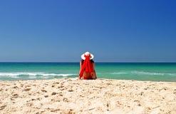 Frau im roten Bikini und im Hut, die im Frieden auf einem schönen sonnigen Strand sitzt. Stockfotografie