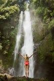 Frau im roten Bikini und im Wasserfall Stockfotografie
