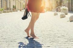 Frau im roten eleganten Kleid, Schuhe des hohen Absatzes in der Hand halten und stockbilder