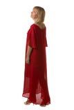 Frau im roten Eleganzkleid, das zurück steht und Seite betrachtet stockbilder