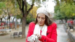 Frau im roten Erhalten kalte und setzende Handschuhe stock video footage