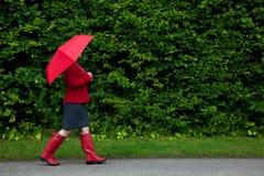 Frau im roten Gehen mit Regenschirm Lizenzfreie Stockbilder