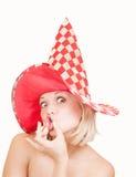 Frau im roten Hut, der ein lustiges Gesicht auf Weiß bildet Stockfotografie