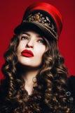 Frau im roten Hut mit goldener Dekoration mit den roten Lippen Stockfotografie