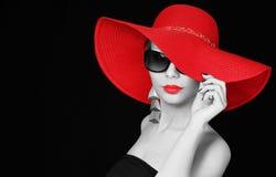 Frau im roten Hut und in der Sonnenbrille über Schwarzem lizenzfreie stockfotos