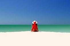 Frau im roten Hut und im Bikini ganz, die alleine auf leerem Strand sitzt Stockfotos