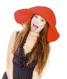 Frau im roten Hut zeigt ihre Zunge Stockbild