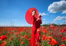 Frau im roten Kimono, der auf dem Mohnblumengebiet aufwirft Lizenzfreie Stockfotografie