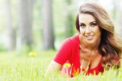 Frau im roten Kleid auf Gras Stockbild