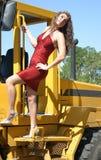 Frau im roten Kleid auf Planierraupe Stockfotos