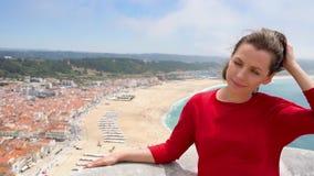 Frau im roten Kleid, das auf einen Hügel über der Stadt von Nazaret, Portugal, Zeitlupe sich entspannt stock video