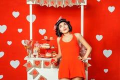 Frau im roten Kleid, das einen Kuchen und Träume hält stockfotos