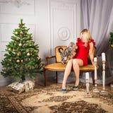 Frau im roten Kleid, das nahe Weihnachtsbaum sitzt Stockfoto