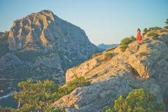Frau im roten Kleid gehend auf Felsen Lizenzfreie Stockfotografie