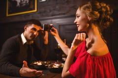 Frau im roten Kleid macht Bild von ihrem Mann am Telefon Stockfoto