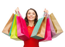 Frau im roten Kleid mit bunten Einkaufstaschen Lizenzfreie Stockfotos