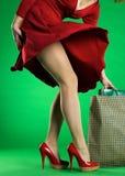 Frau im roten Kleid mit Einkaufstasche Stockbild