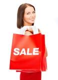 Frau im roten Kleid mit Einkaufstaschen Lizenzfreie Stockfotos