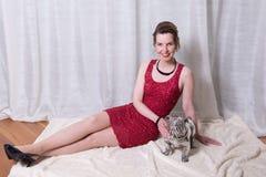 Frau im roten Kleid mit Hund auf Decke Stockfotografie