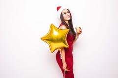 Frau im roten Kleider- und Sankt-Weihnachtshut mit Golddem sternförmigen Ballonlächeln Stockbild