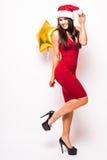 Frau im roten Kleider- und Sankt-Weihnachtshut mit Goldsternförmigem Ballon Stockbild