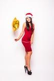 Frau im roten Kleider- und Sankt-Weihnachtshut mit Goldsternförmigem Ballon Lizenzfreie Stockfotos