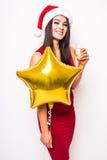 Frau im roten Kleider- und Sankt-Weihnachtshut mit lächelndem und trinkendem Champagner des Goldsternförmigem Ballons Lizenzfreie Stockbilder