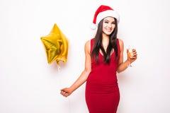 Frau im roten Kleider- und Sankt-Weihnachtshut mit lächelndem und trinkendem Champagner des Goldsternförmigem Ballons Lizenzfreies Stockfoto