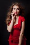 Frau im roten Kleiderporträt lokalisiert auf schwarzem Hintergrund Stockfoto
