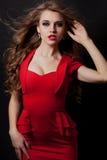 Frau im roten Kleiderporträt lokalisiert auf schwarzem Hintergrund Stockbild