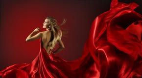 Frau im roten Kleidertanzen, Mode-Modell mit Fliegen-Gewebe Stockbild