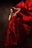 Frau im roten Kleidtanzen mit Flugwesengewebe Stockfotografie
