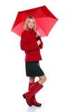 Frau im roten Mantel, in den Matten und im Regenschirm Stockbild