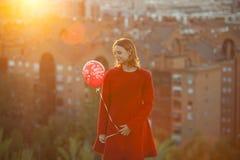 Frau im roten Mantel, der einen Weihnachtsballon hält Lizenzfreie Stockfotos