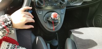 Frau im roten Minikleid, das auf Fahrersitz ihre Hand auf Lenkrad sitzt stockfotografie