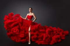 Frau im roten Rüschenkleid, Mode-Modell im langen flaumigen wellenartig bewegenden Kleid stockfotografie